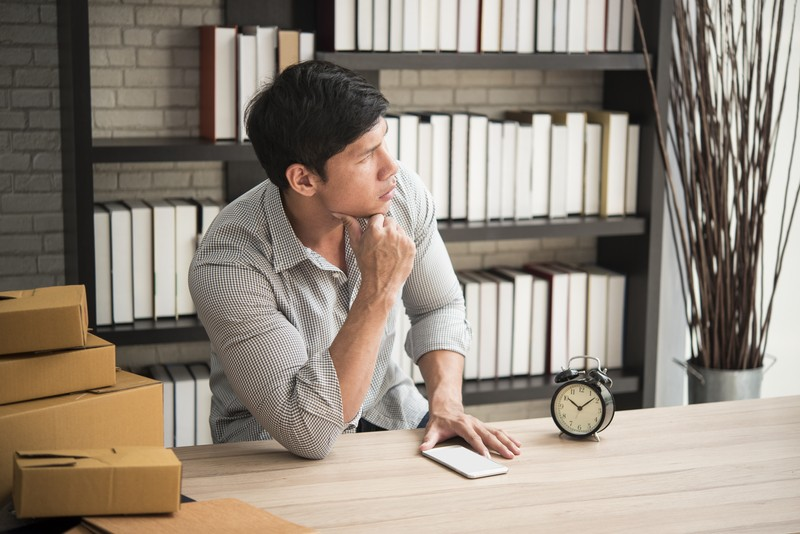 Young man sitting in a home office with thinking.